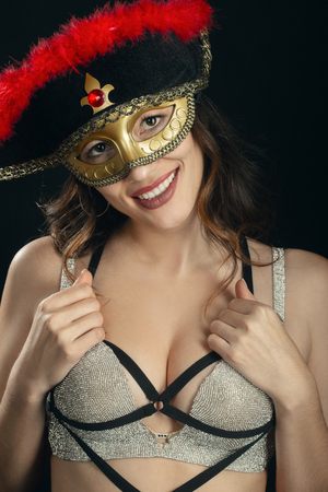 happy woman with masquerade mask and bra on black background looking at camera, smiling