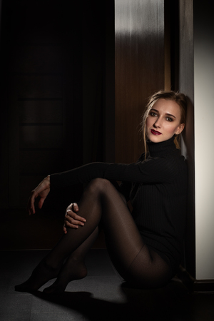 sensual beautiful young woman in black dress and tights sitting on wooden floor in dark room looking at camera