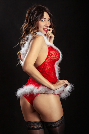 sensual young woman in miss santa costume on black background show her buttocks, looking at camera