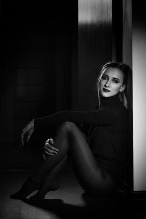 sensual beautiful young woman in black dress and tights sitting on wooden floor in dark room looking at camera, monochrome