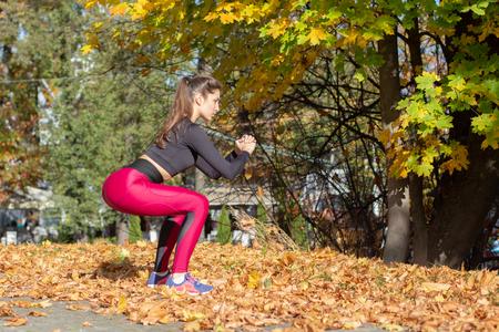 slim sports woman squat in autumn city park