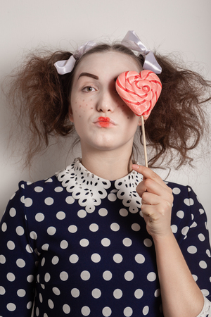 girl with bright makeup on white background make fun face cover her eye with red lollipop Archivio Fotografico