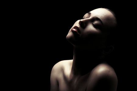 sensual aroused woman with bare shoulders, closed eyes on black background