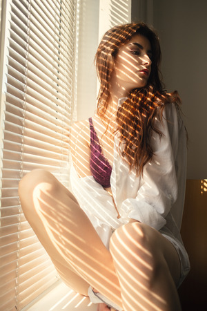 sensual girl in lingerie near window in sunlight with blinds shadows Stock Photo