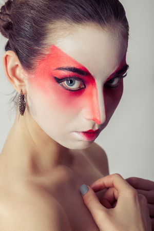 serious young woman with professional geisha makeup and bare shoulders looking at camera 写真素材
