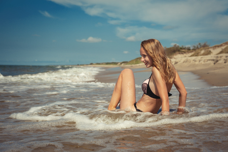 blond girl in swimsuit sitting at sea beach tanning