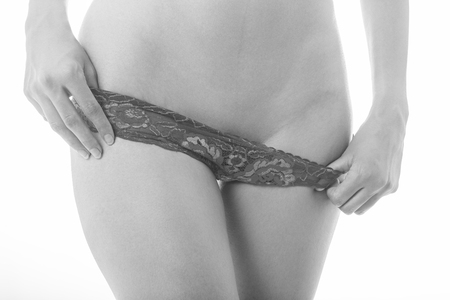 woman move panties down show her hairless body after shugaring, monochrome