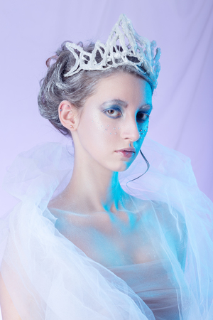 sensual young woman in crown with snow ice queen makeup with multicolor lights on pink background