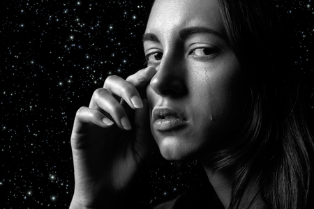 sad woman crying on stars background, looking at camera, closeup portrait Stock Photo