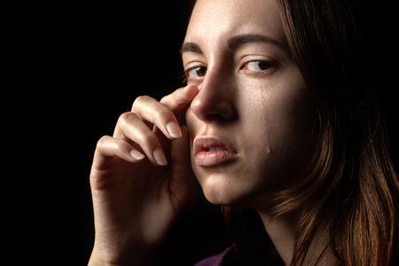 Traurige Frau weint auf schwarzem Hintergrund, Blick in die Kamera, Nahaufnahmeportrait Standard-Bild