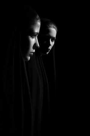 serious young women nuns in hood on black background, profile view and looking at camera