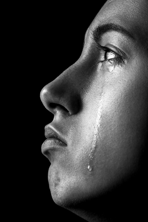 sad woman crying, looking up on black background, closeup portrait, profile view