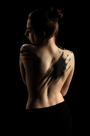 young woman with dirty black paint hands cover her body, closed eyes, rear view