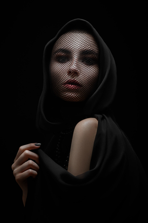 serious female beautiful face with stocking on head looking at camera on black background Imagens