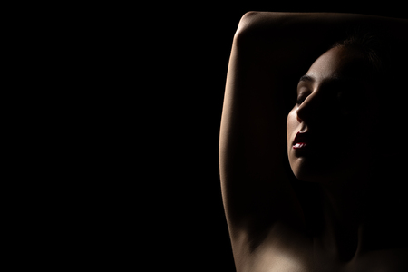 sad young woman with closed eyes on black background with copy space with back light Stock Photo