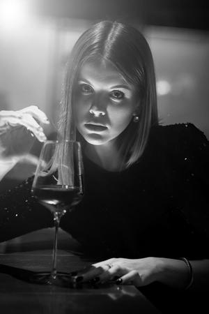 single luxury beautiful woman sitting with wine near bar in restaurant, monochrome Imagens