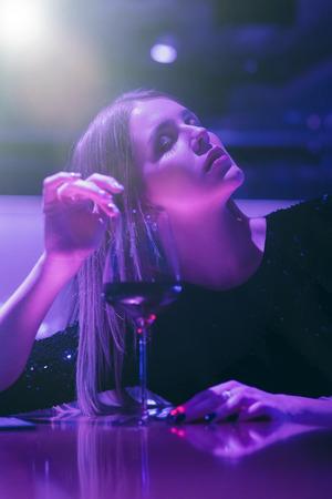 single luxury beautiful woman sitting with wine near bar in restaurant, ultraviolet toned image Banco de Imagens - 119542728