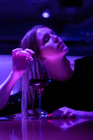 single luxury beautiful woman sitting with wine near bar in restaurant, ultraviolet toned image Banco de Imagens - 121036878