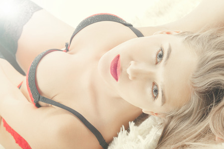 sensual aroused woman in lingerie lying on bed, looking at camera Фото со стока