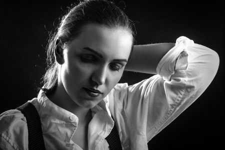 sad serious woman in white blouse looking down on black background Foto de archivo