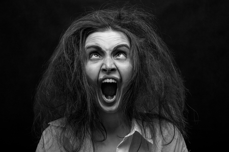 fun crazy young woman with fluffy hair on black background make grimace screaming, monochrome Stockfoto