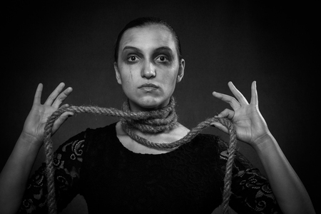 serious woman with rope on neck at black background looking at camera
