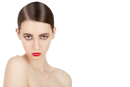 serious elegant brunette woman with luxury makeup and bare shoulders isolated on white background with copy space looking at camera