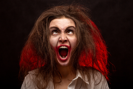 fun crazy young woman with fluffy hair on black background make grimace screaming