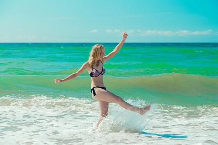 einzelne glückliche junge Frau im Badeanzug, die mit Schaum und Spritzern auf See surft Standard-Bild
