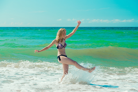 single happy young woman in swimsuit jumping at sea surf with foam and splashes 版權商用圖片