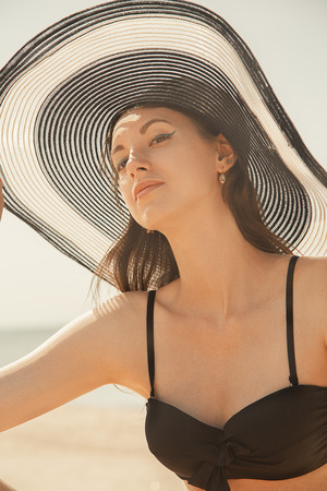 beautiful sensual young woman in hat looking at camera under sun rays tanning, toned image