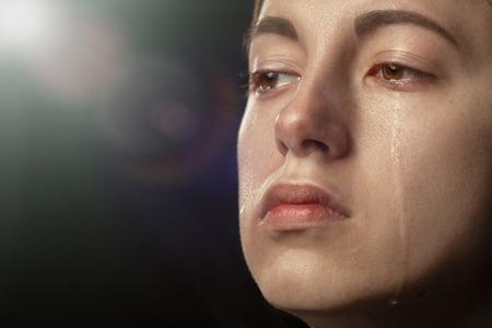 sad woman crying on black background with light rays, closeup portrait Фото со стока - 121593940