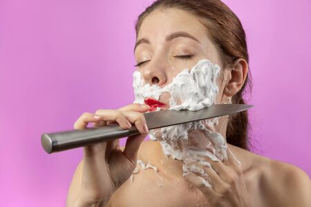 fun young woman has shave with knife on pink background, closed eyes