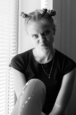 fun angry young woman sitting on window making grimace looking at camera, monochrome