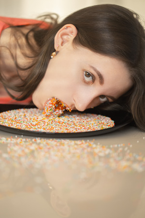 girl licking multicolored sugar balls on plate looking at camera Stok Fotoğraf