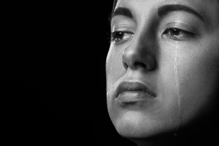 Mujer triste llorando sobre fondo negro, primer retrato, monocromo