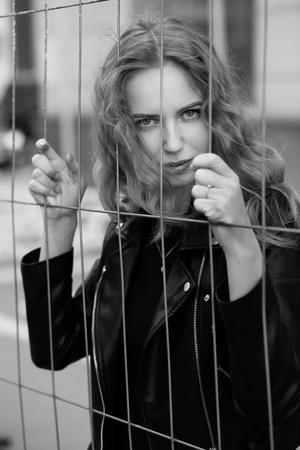 sad blond girl behind metal bars looking at camera, monochrome Stock Photo