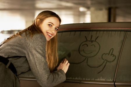 fun blond young woman drawn fuck gesture on dirty car window smiling looking back