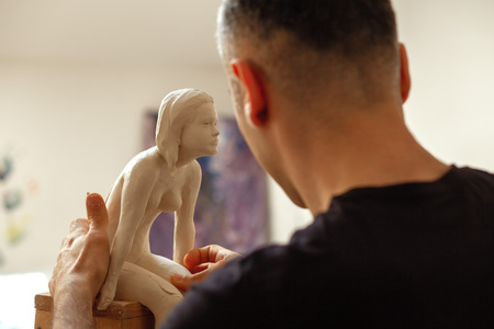 sculptor making the girl's figurine of white clay Reklamní fotografie