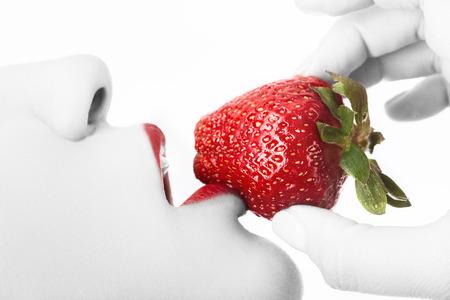 Jeune femme sensuelle avec la bouche ouverte et la fraise juteuse sur fond blanc vue de profil isolée