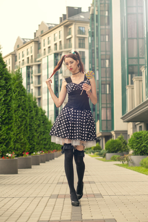 attractive young woman with candy in black dress walking on street