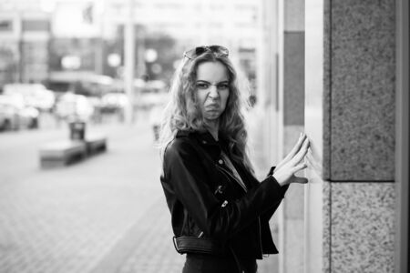 fun sad serious blond woman in leather coat stand on street grimacing looking at camera, monochrome Banco de Imagens