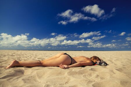 young blond woman tanning on sand sea beach under sun rays Фото со стока