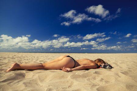 young blond woman tanning on sand sea beach under sun rays Standard-Bild