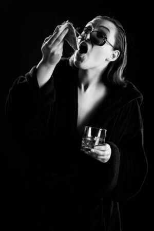 fun young woman in bathrobe eats pizza and whiskey, black background, monochrome Banco de Imagens