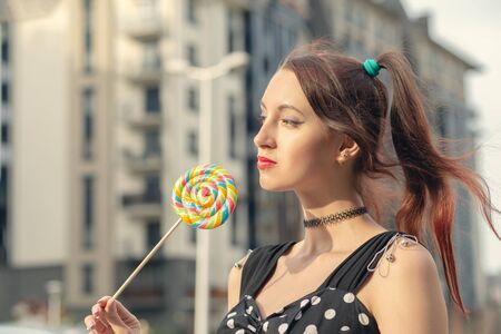 attractive young woman with lollipop in black dress posing on street