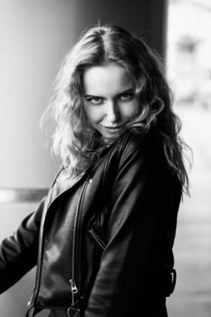 happy cute blond woman in leather coat stand on street looking at camera smiling, monochrome