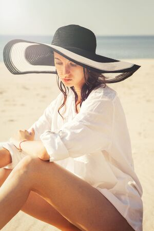beautiful young woman in hat and blouse at sand sea beach under light rays