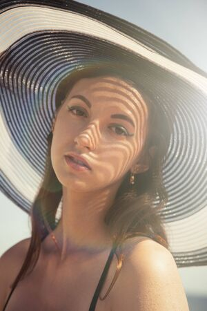 beautiful sensual young woman in hat looking at camera under sun rays, toned image