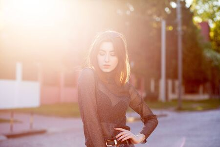 beautiful young woman on street in sunny backlight